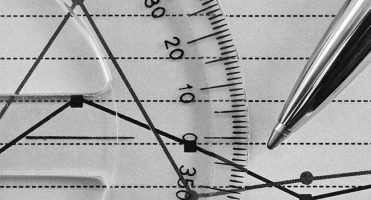 The image is zoomed in on a protractor and a pen.