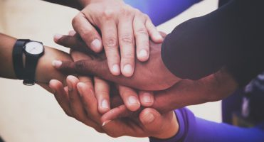 The image features six diverse hands stacked on top of one another.