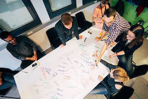 This image features a group of 6 people collaborating on a large piece of white paper on a table.