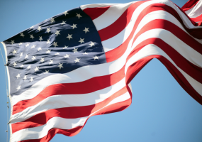 The image features the American flag blowing in the wind.