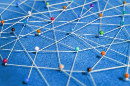 white thread connected around pins with different colored heads to help see how ideas travel