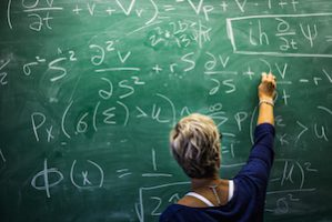 The image features a woman writing math calculations on a large chalkboard.