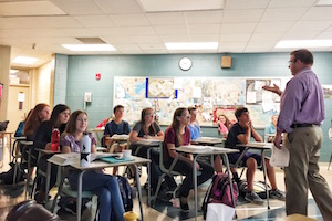 The image features a classroom of teenagers sitting at their desk while a teacher talks in front of them.