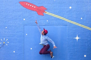 This image features a young boy jumping in the air, in front of a blue wall with a red rocketship painted on it.